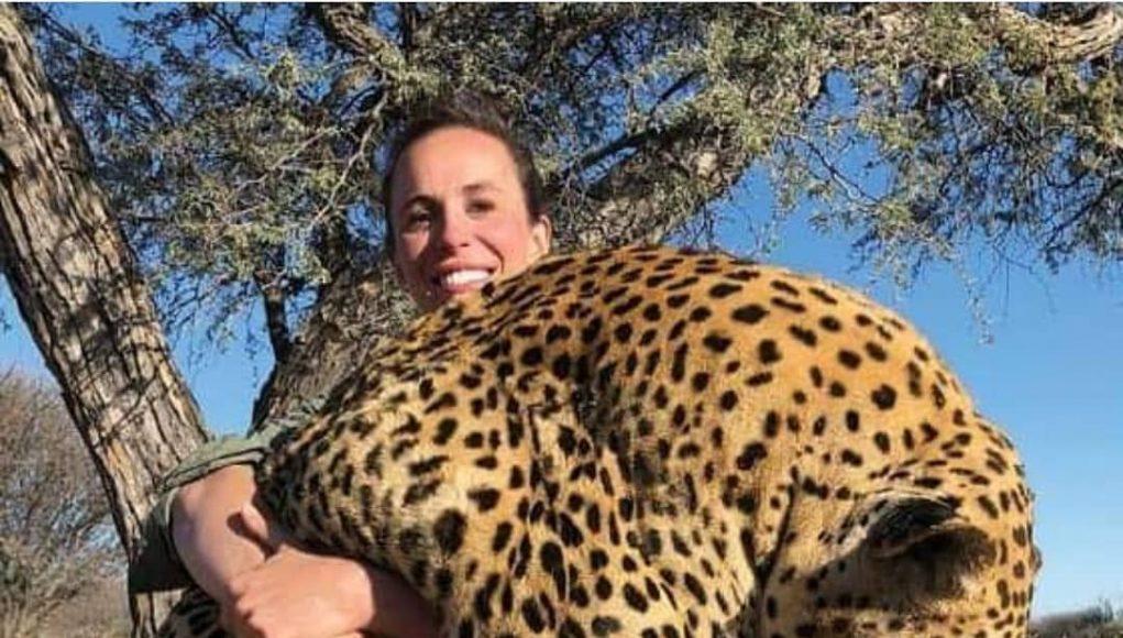 Mit strahlendem Lächeln zeigt eine Jägerin ihren erlegten Leopard